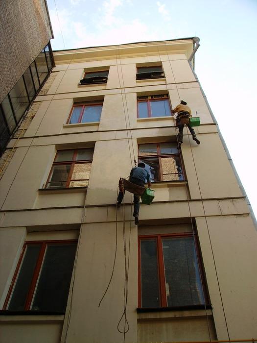 Окраску фасада дома выполняют специализированные альпинисты